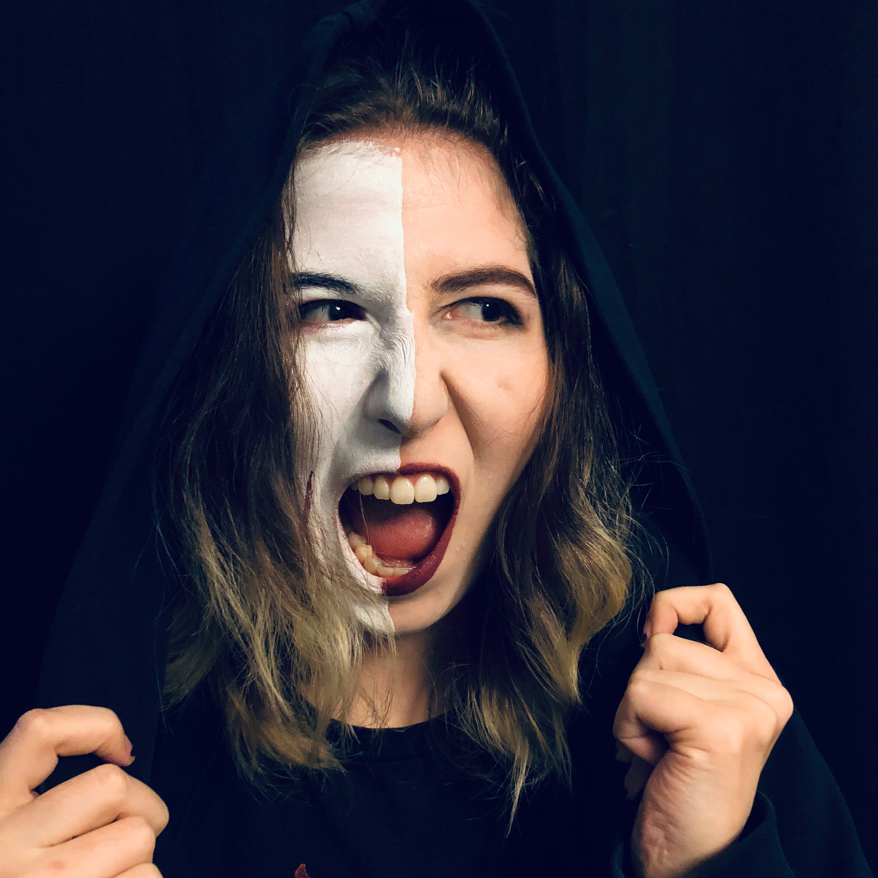 KaseyDidWhat appears to be screaming as she holds a black hood over he head, white facepaint on the right sisde of her face. Her shirt is black as well as the background, making it a very moody and dramatic shot.